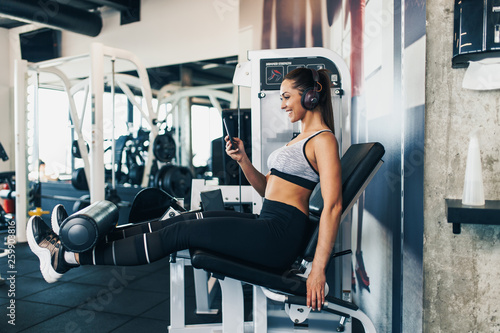 Fototapeten Fitness Young fit and attractive woman working out in modern gym and listening to music with bluetooth headphones and smart phone.