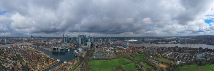 Aerial drone shot from iconic Canary Wharf skyscraper business and financial area with lots of clouds, Docklands, Isle of Dogs, London, United Kingdom © aerial-drone