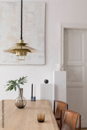 Eclectic and elegant dining room interior with design sharing table, chairs, gold pendant lamp, abstract paintings and stylish accessories. Tropical leafs in vase.Eclectic decor. Brown wooden parquet. - 259920296