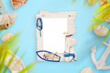 Photo frame on blue desk surrounded with smmer, travel, sea decorations. - 259921810