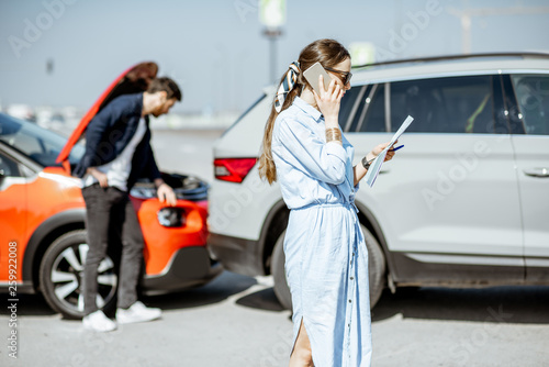 Leinwanddruck Bild Woman calling road assistance or insurance company standing on the road after the car collision, man checking the damage