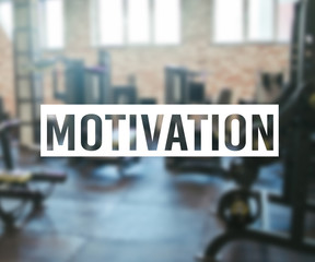 Word Motivation on blurred background of gym with equpment.