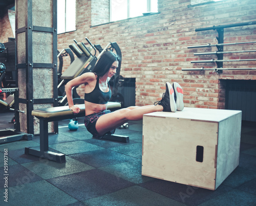 Fototapeten Fitness Young brunette in sportswear doing rear push ups for triceps from bench. Training with your weight in the gym