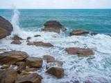Waves crashing on coastal stones at sunrise.Thailand.