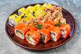 Fototapeta Tęcza - Rainbow Sushi Roll with salmon, eel, tuna, avocado, royal prawn, cream cheese Philadelphia, caviar tobica, chuka. Sushi menu. Japanese food © Maksim Shebeko