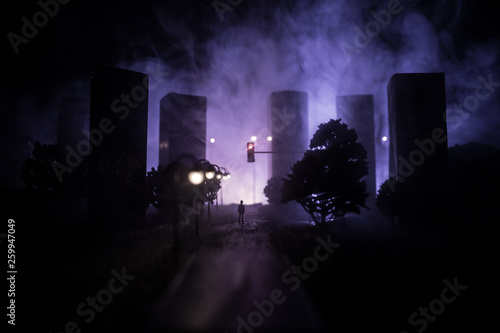 Artwork decoration. A man standing on a road of burnt up city. Apocalyptic view of city downtown as disaster film poster concept. Night scene. City destroyed by war. - 259947049
