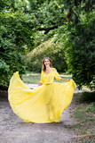 Incredible beautiful dancer in a long yellow dress. Fashion and beauty dancer. A girl in a yellow dress is dancing in a flowered park.