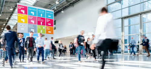 blurred business people at a trade fair hall © rcfotostock