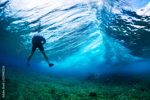 Underwater photographer floats in the wave with big wave breaking in the frame