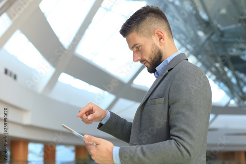 Businessman working in office with transparent tablet and laptop. © ty