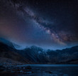 Composite image of Winter landscape of snowcapped Mountain Range at night with Milky Way above