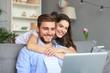 Leinwandbild Motiv Young couple doing some online shopping at home, using a laptop on the sofa.