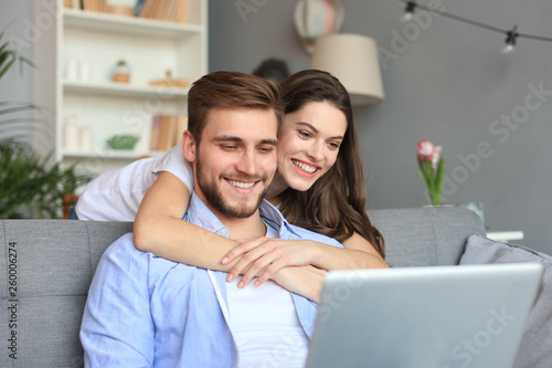 Young couple doing some online shopping at home, using a laptop on the sofa. © ty