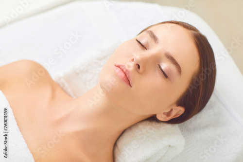 Leinwandbild Motiv Beauty and spa concept. Brunette girl lying on a massage desk