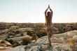 Leinwanddruck Bild - Young woman is practicing yoga at mountain