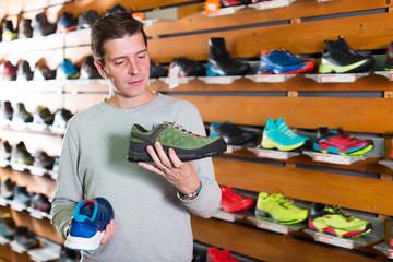 Positive man chooses shoes in shop
