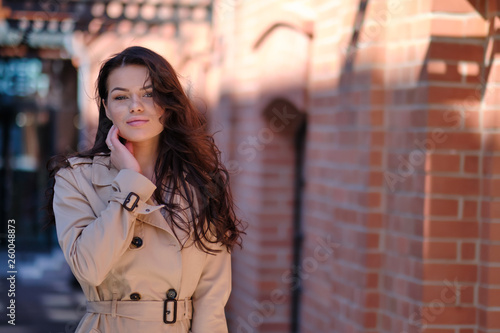 fototapeta na ścianę Stylish and cheerful. Beautiful young woman looking at camera with smile while standing outdoors