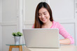 Young asian woman using laptop computer and smiling with happiness , people and technology, lifestyles, education, business concept