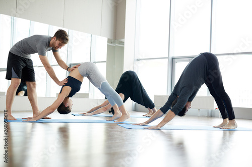 Leinwandbild Motiv Content handsome young qualified yoga coach assisting students at class: he correcting downward facing dog pose of young woman