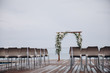 Quadro arch for the wedding ceremony and chairs for guests stand on the background of water