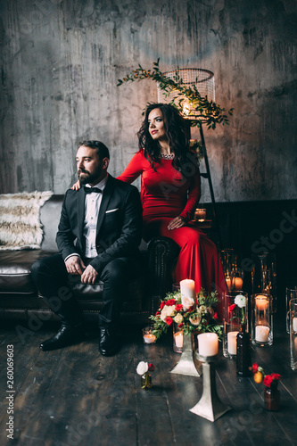 Photo session of the newlyweds in the studio. Red dress and black suit.