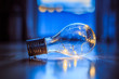 Ideas and innovation: Light bulb with LEDs is lying on the wooden floor. Window and light in the blurry background.