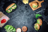 Fresh and tasty sandwiches with ham, prosciutto, cheese, lettuce salad and vegetables on dark background and copy space