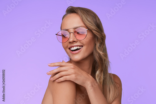 Portrait of beautiful young woman with perfect makeup wearing pink sunglasses. Smiling fashion model in aviator sunglasses posing on lilac background. Studio shot. Summer vacation. © YURII MASLAK