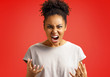 Leinwandbild Motiv Annoyed girl gestures and shouts in anger. Photo of african american girl wears casual outfit on red background. Emotions and pleasant feelings concept.