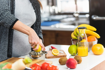Pregnant woman preparing healthy food with lots of fruit and vegetables at home. Close-up.