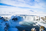 Scenic landscape view of tourist popular attraction Godafoss waterfall in northern Iceland in winter time. Long exposure falling water photo, snow covered mountains on background.