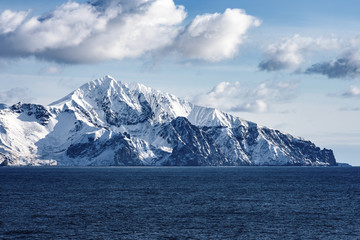 Snow peaks, glaciers and rocks of Aleutian islands in sunny winter day as viewed from ship passing in calm sea