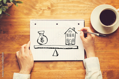 House and money on the scale with a person holding a pen on a wooden desk - 260136038