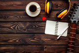 Musician work place with guitar, earphones, notebook and coffee on wooden background top view mock up