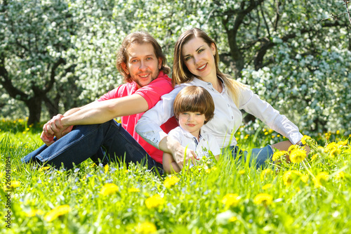 canvas print picture Young family sitting on the grass
