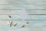 Seashells, sea salt and star on blue wooden background and sheet of paper as a vacation concept with copy space - 260150210