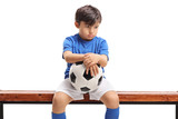 Sad little boy with a football sitting on a wooden bench