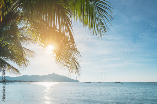 fototapeta na ścianę Coconut plam tree with sun and blue sky at tropical beach, Summer vacation concept
