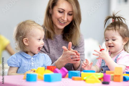 Leinwandbild Motiv Woman teaches children modeling plasticine in day care center