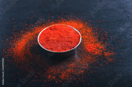 Red Chili pepper flakes and chili powder burst on black background © Niks Ads