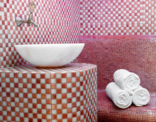 Traditional Turkish hamam with stone walls, sink and stack of  towels