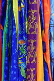 Colorful sarong scarves hanging on display in a market