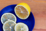 Composition with lemons on a wooden background. Lemons on a blue plate.Fresh yellow lemons, sliced into rings. A few slices of lemon on a wooden cutting board