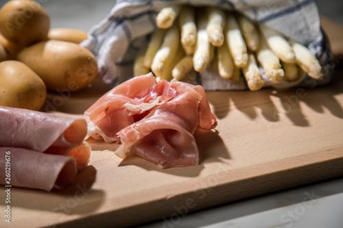 Roher, weißer Spargel in Tuch mit Kochschinken, geräucherten Schinken und Kartoffeln auf Holz Brett und Marmor Hintergrund - 260219676