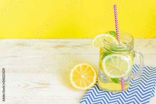 Leinwandbild Motiv Mason jar glass of homemade lemonade with lemons, mint and red paper straw on wooden rustic background. Summer refreshing beverage.