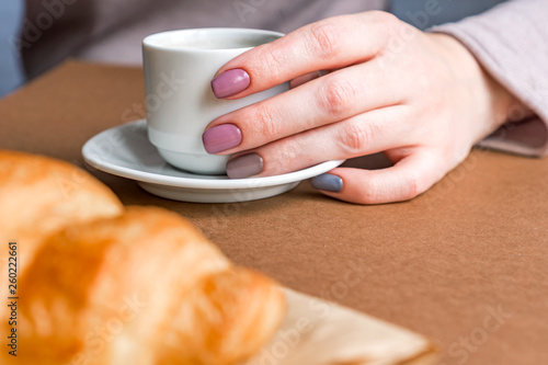Female hands with manicure holding cup of coffee and eating croissant. Breakfast in french style
