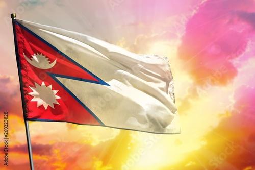 fototapeta na ścianę Fluttering Nepal flag on beautiful colorful sunset or sunrise background. Success concept.