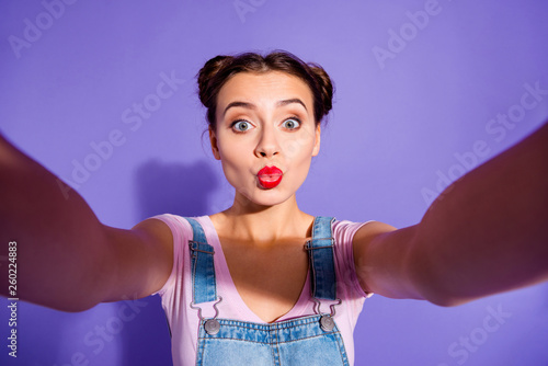 Leinwandbild Motiv Close up photo beautiful amazing she her lady buns head make take selfies modern technology send air kisses people wear casual t-shirt jeans denim overalls clothes isolated purple violet background