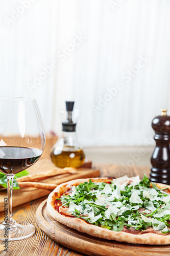 Close up view on fresh served pizza with prosciutto on a wooden table on light background. Pizza with wine. Vertical image with copy space for text. Food for menu. Italian cuisine.  - 260229643