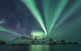 Aurora Borealis across a mountain range on Senja from Husøy, northern Norway